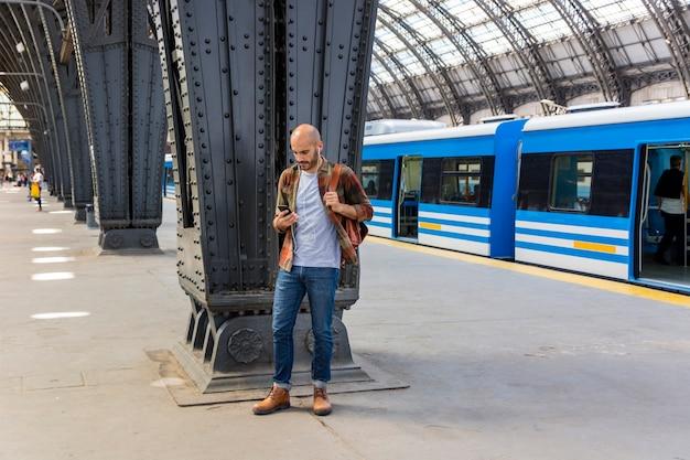 Man at subway using smartphone Free Photo