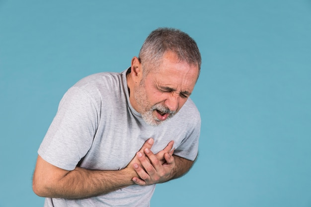 Man suffering from chest pain on blue backdrop Premium Photo