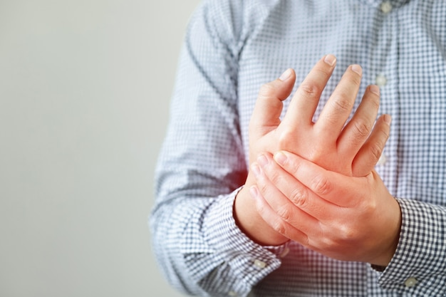 Человек страдает от боли в руке, боли в костях Premium Фотографии