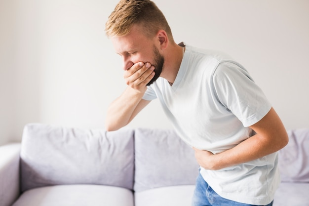 Man suffering from vomit and closing mouth Free Photo