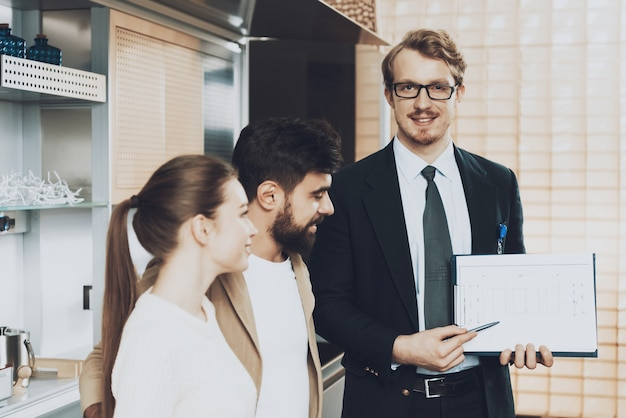 Man in suit looking at camera showing blueprints to clients. Premium Photo