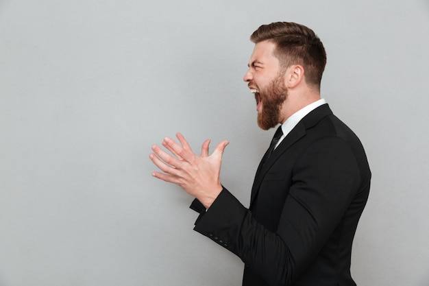 Man in suit shouting and gesturing with hands Free Photo