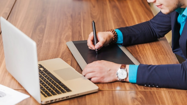Man in suit sitting at desk drawing Free Photo