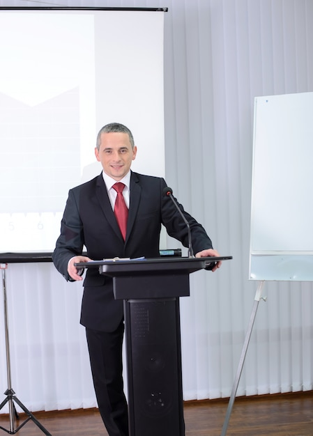 A man in a suit stands behind the podium and says. Premium Photo
