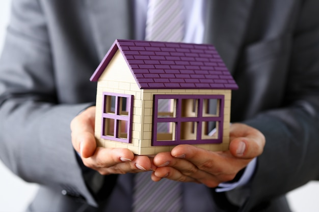 Man in suit and tie cover with arms little toy house Premium Photo