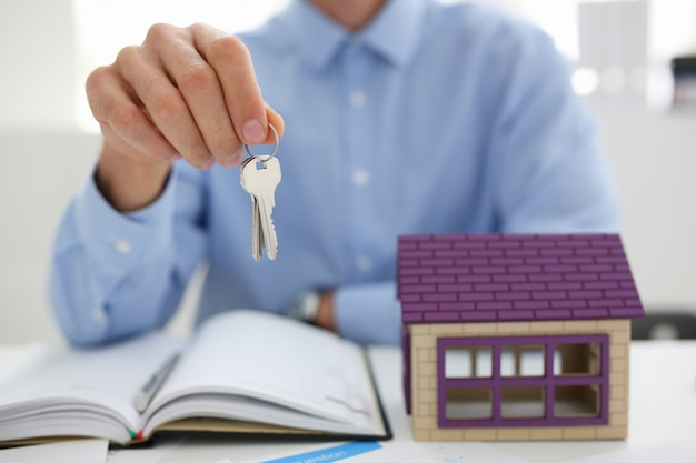 Man in suit and tie hold in hand silver key giving Premium Photo