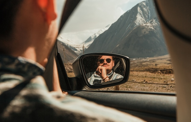 Man in sunglasses looking at the mountains with car window reflected in the mirror Free Photo