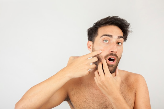 Man surprised with a new pimple Free Photo