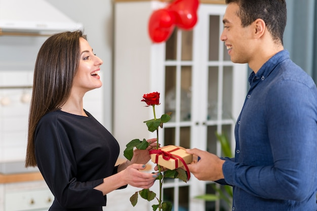 Man surprising his girlfriend with a valentine's day gift Free Photo