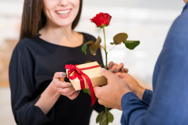 Man surprising his smiley girlfriend with a valentine's day gift Free Photo