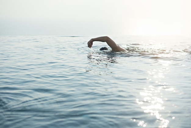A man swimming for exercise in at swimming pool Premium Photo