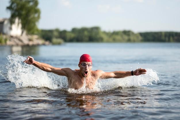 Uomo che nuota nel lago Foto Gratuite