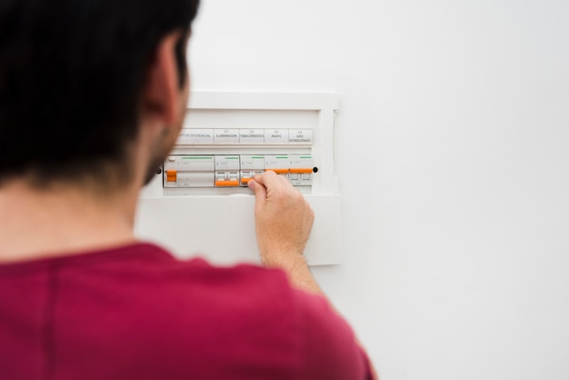 Man switching off electric fuse in electrical box on wall Free Photo
