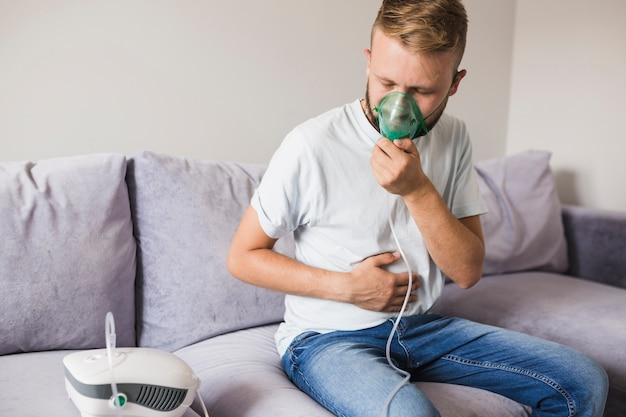 Man in t-shirt using asthma nebulizer Free Photo