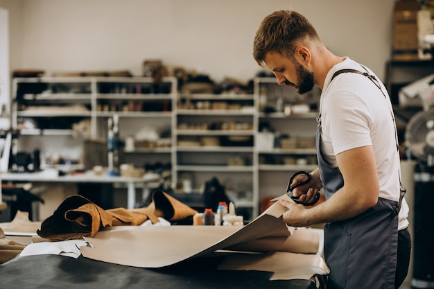Man tailor working with leather fabric Free Photo