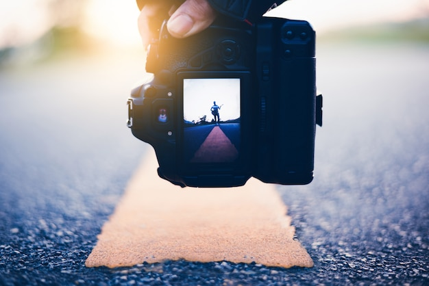 Man take a photo of young man sitting on road and playing guitar, journey of musician concept Premium Photo