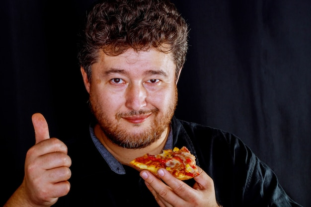 Man in takes an appetizing hands take a delicious piece of pizza. Premium Photo