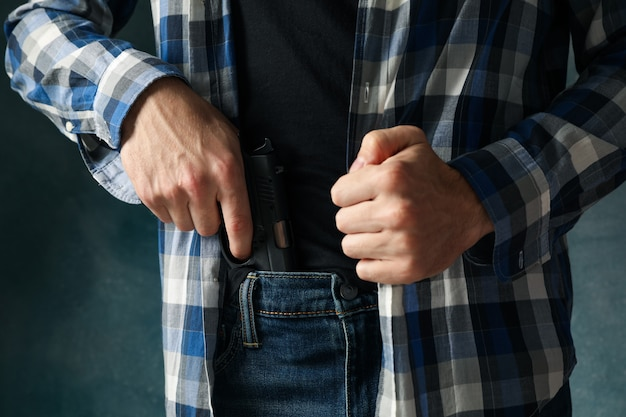 Man takes out a gun from jeans, close up. robber Premium Photo