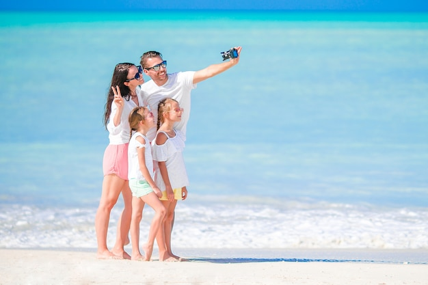 ビーチで彼の家族の写真を撮る男。家族での休暇 Premium写真
