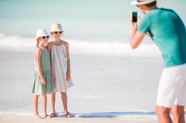 ビーチで彼の子供たちの写真を撮る男 Premium写真