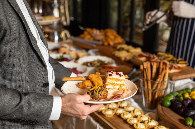 Мужчина принимает пищу со стола для завтрака в ресторане Premium Фотографии