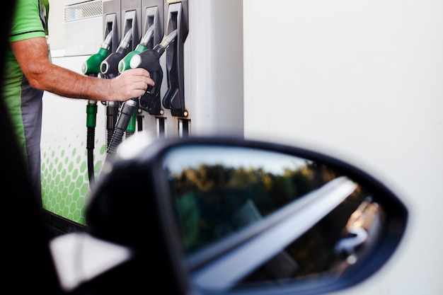 Man taking a gas pump to refill Free Photo