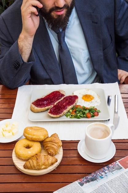 Man taking on mobile phone while having breakfast Free Photo
