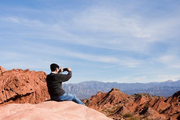 Man taking a photo at mountain landscape Free Photo