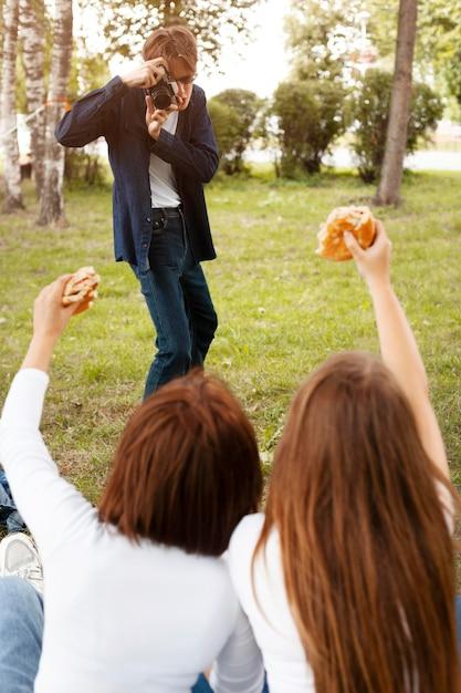 Мужчина фотографирует своих друзей, пока они держат гамбургеры Бесплатные Фотографии