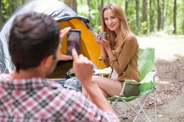 Человек фотографирует свою девушку в лесу Бесплатные Фотографии