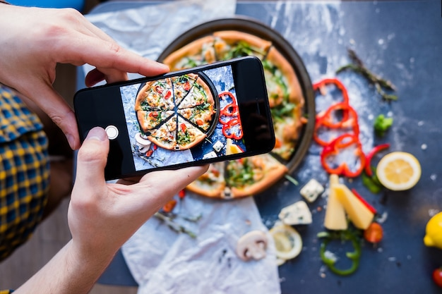 Man taking photo of pizza with smartphone closeup view of process Premium Photo