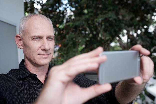Man taking photo on smartphone Free Photo