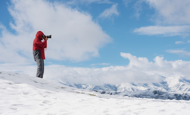 Man taking photo on the snow with mountain view in winter Premium Photo