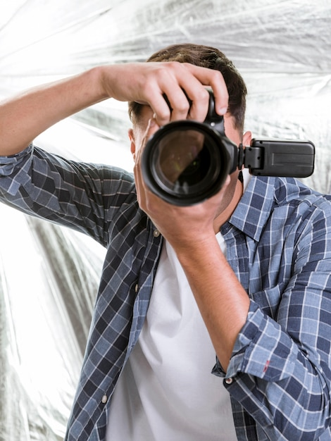Man taking a photo with a professional camera Free Photo