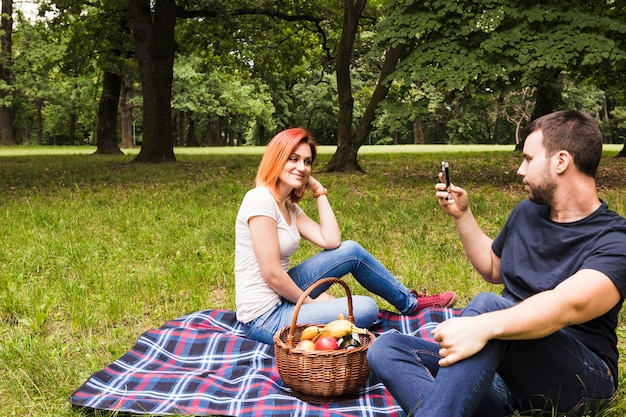 Man taking photograph of her smiling girlfriend on smartphone at picnic Free Photo