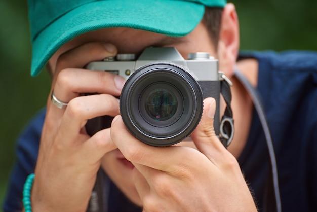 Man taking photos with retro style camera Premium Photo