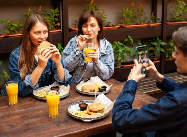 ハンバーガーを食べる女性の友人の写真を撮る男 Premium写真