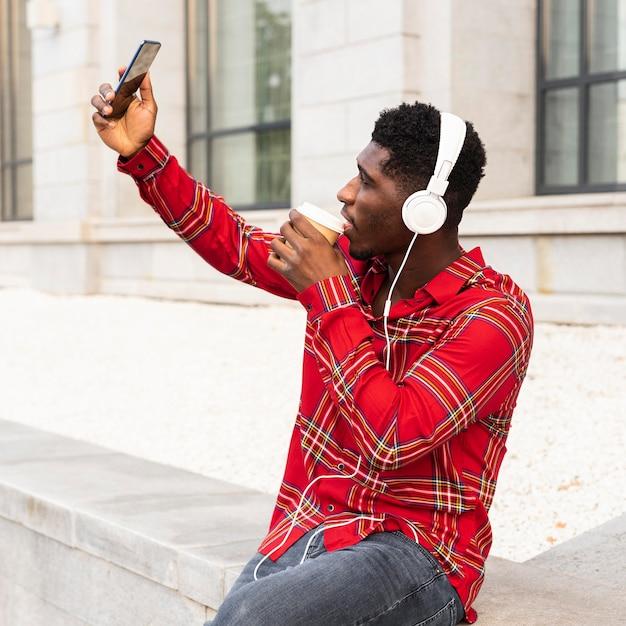 Uomo che prende un selfie e ascolta la musica Foto Gratuite