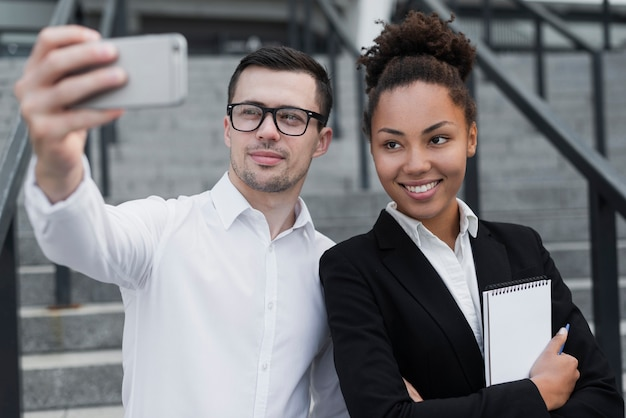Man taking selfie with coworker Free Photo