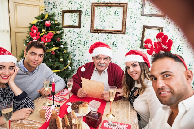 Man taking selfie with family at festive table Free Photo