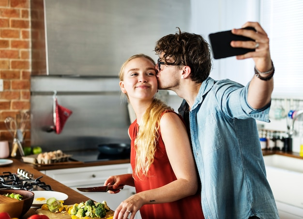 Man taking a selfie with his wife in the kitchen Premium Photo