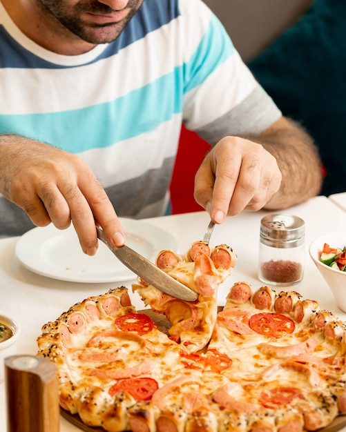 Man taking a slice from sausage pizza Free Photo