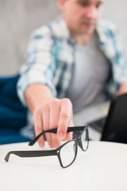 Man taking stylish glasses from table Free Photo