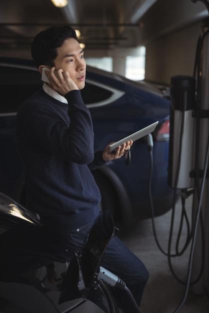 電気自動車を充電しながら携帯電話で話している男 無料写真