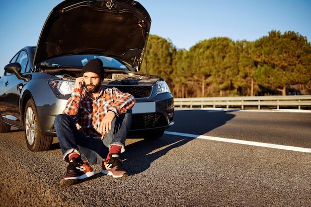 車の横にある電話で話している男性 無料写真