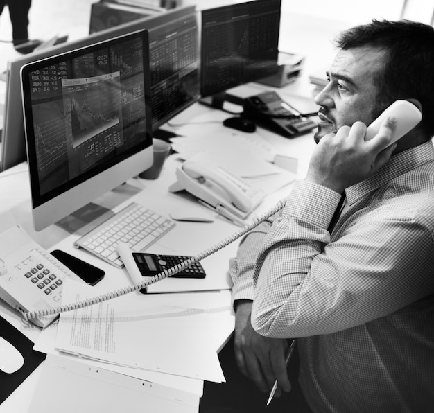 Man talking on the phone looking at stock market analysis on computer screen Free Photo