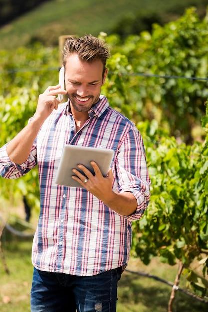 Man talking on phone while using tablet at vineyard Premium Photo