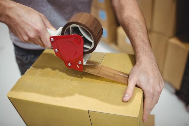 Man taping box in warehouse Premium Photo