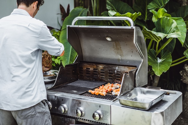 A man in tattoos makes barbecue grill meat outdoors. Free Photo