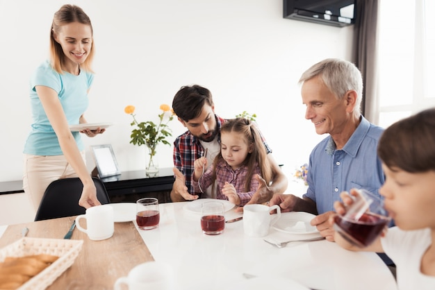 Man teaches girl to use fork boy drinks juice from a glass Premium Photo